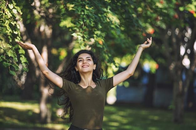 Jong volwassen mooi donkerbruin meisje in vrijetijdskleding blij voor een wandeling in het park