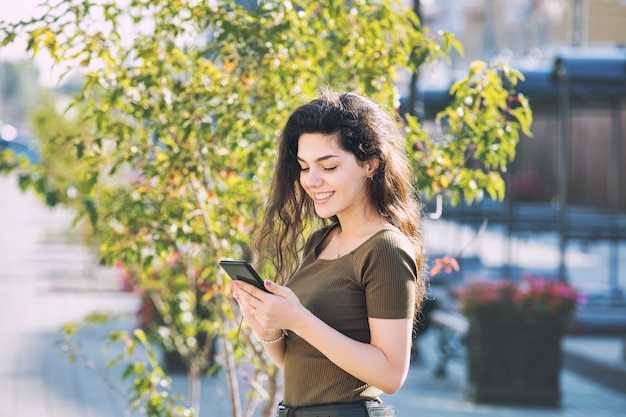 Jong volwassen mooi donkerbruin meisje in vrijetijdskleding met mobiele telefoon gelukkig op stadsstraat