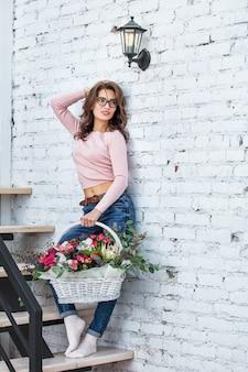 Jong volwassen mooi en gelukkig vrouwenmodel met bloemen in haar handenportret op een heldere trap