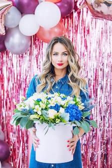 Jong volwassen mooi en gelukkig vrouwenmodel met bloemenportret op feestelijke achtergrond