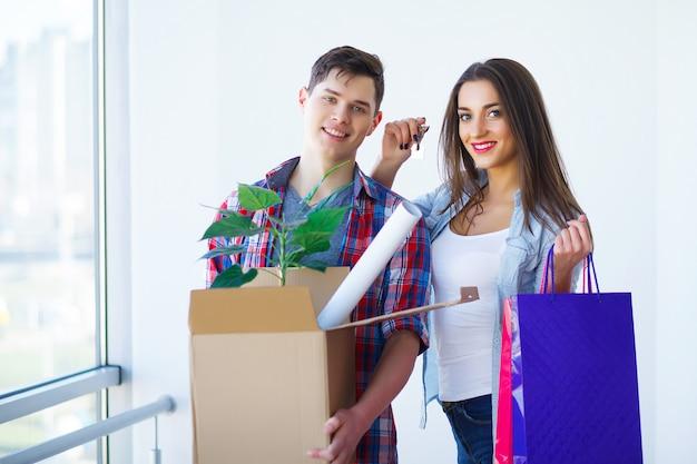 Jong volwassen paar binnen zaal met dozen die de banner van nieuw huissleutels houden.
