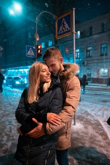 Jong volwassen paar dat op sneeuw behandelde stoep loopt
