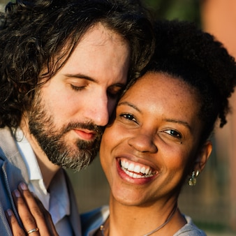Jong volwassen paar tussen verschillende rassen op een strand, een blanke man en een afro-amerikaanse vrouw in casual kleding
