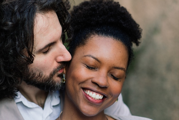 Jong volwassen paar tussen verschillende rassen op een strand, een kaukasische mens en een afrikaans amerikaans wijfje in vrijetijdskleding die van de zomerdag op kust genieten