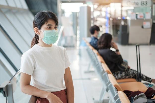 Jong volwassen wijfje dat gezichtsmasker in luchthaventerminal draagt