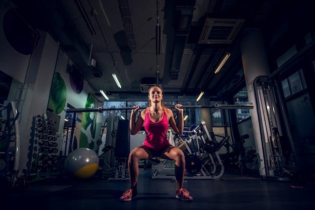 Jong vrij actief vormmeisje die hurkzitoefening met een bar achter de hals in de gymnastiek doen.