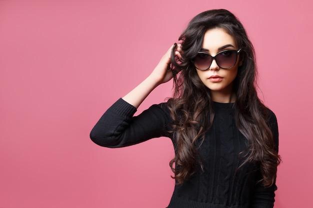 Jong vrij sexy vrouw of meisje met leuk gezicht en lang donkerbruin haar die zonnebril en zwarte sweater dragen, die op roze achtergrond stellen