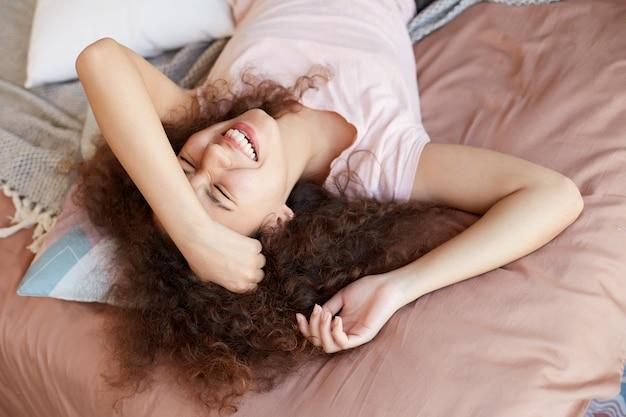 Jong vrolijk afrikaans amerikaans krullend meisje dat de zonnige dag thuis doorbrengt, op het bed ligt en in grote lijnen glimlacht.
