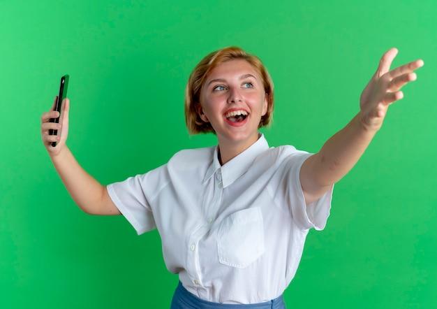 Jong vrolijk blond russisch meisje houdt telefoon en wijst naar voren met hand geïsoleerd op groene achtergrond met kopie ruimte