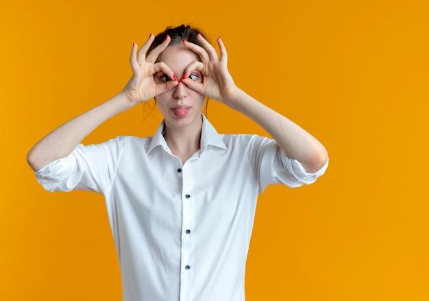 Jong vrolijk blond russisch meisje kijkt door vingers en steekt tong uit op sinaasappel met exemplaarruimte