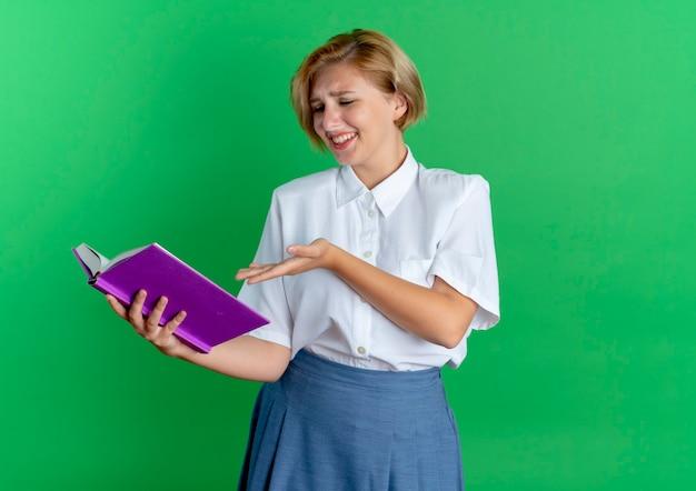 Jong vrolijk blond russisch meisje kijkt en wijst naar boek dat op groene achtergrond met exemplaarruimte wordt geïsoleerd