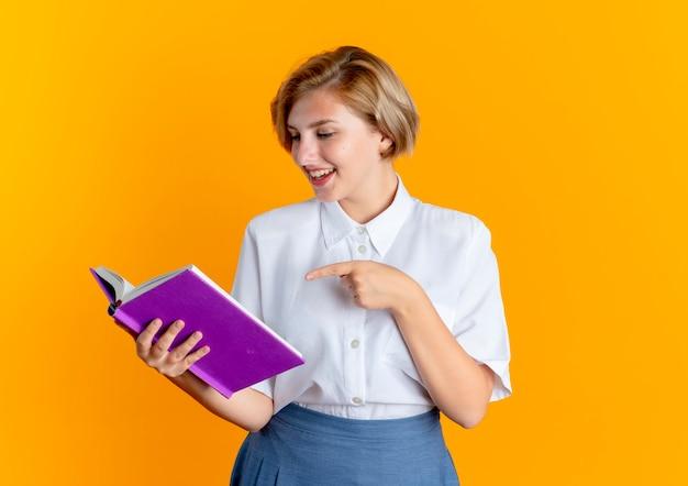 Jong vrolijk blond russisch meisje kijkt en wijst naar boek dat op oranje achtergrond met exemplaarruimte wordt geïsoleerd