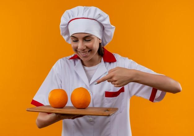 Jong vrolijk kaukasisch kokmeisje in eenvormige chef-kok houdt en wijst naar sinaasappelen op scherpe raad die op oranje ruimte met exemplaarruimte wordt geïsoleerd