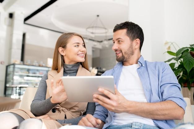 Jong vrolijk koppel met digitale tablet kijken elkaar terwijl overleggen over wat te kijken op hun gemak in café