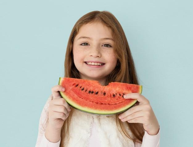 Jong vrolijk meisje dat een plak van watermeloen houdt