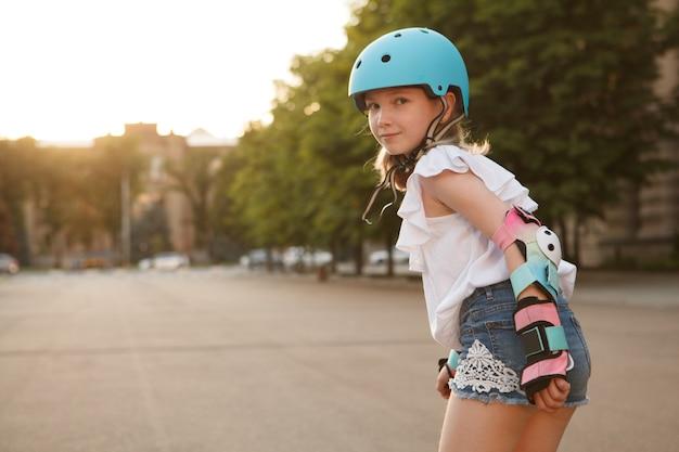 Jong vrolijk meisje lacht naar de camera over haar schouder tijdens het skaten, met beschermende kleding