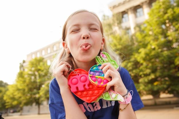 Jong vrolijk meisje steekt speels haar tong uit en houdt pop it fidget toys vast