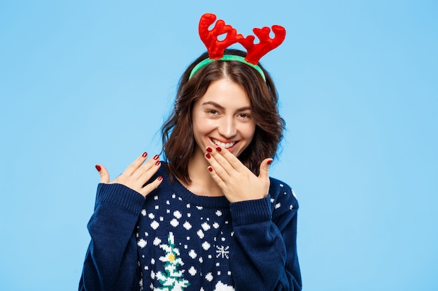Jong vrolijk mooi donkerbruin meisje in gebreide sweater en kerstmisrendiergeweitakken die over blauwe muur glimlachen
