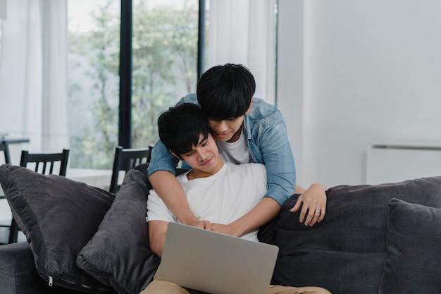Jong vrolijk paar die computerlaptop met behulp van bij modern huis. aziatische lgbtq + mannen gelukkig ontspannen plezier met behulp van technologie kijken naar film op internet samen terwijl liggend bank in de woonkamer in huis.