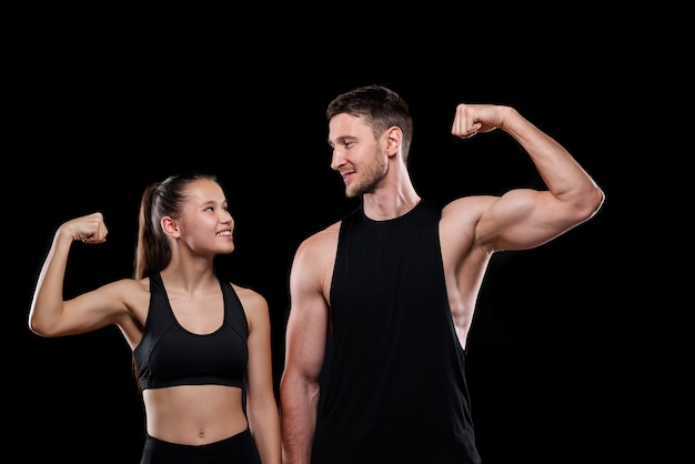 Jong vrolijk sportenpaar in activewear die elkaar bekijken terwijl zij hun kracht tonen