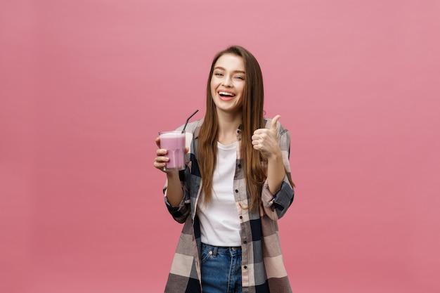 Jong vrouw het drinken sap smoothie met stro. geïsoleerde studio portret.