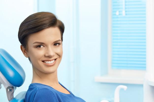 Jong vrouwelijk geduldig bezoekend tandartsbureau. mooie glimlachende vrouw die met gezonde rechte witte tanden bij tandstoel zit. tandarts. stomatology
