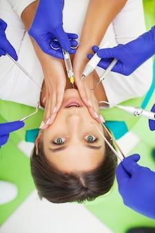 Jong vrouwelijk geduldig bezoekend tandartsbureau. vrouw die tanden heeft die bij tandartsen worden onderzocht