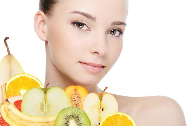 Jong vrouwelijk gezicht met vers fruit dat op wit wordt geïsoleerd