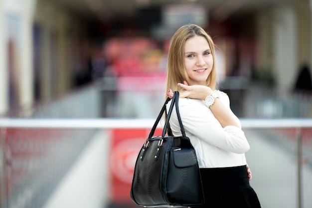 Jong vrouwelijk model in stijlvolle outfit holding handtas