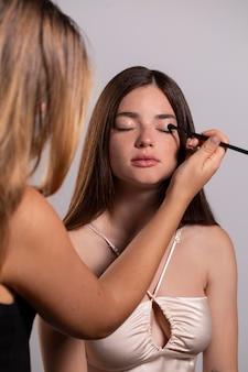 Jong vrouwelijk model laat zich opmaken door een professionele artiest