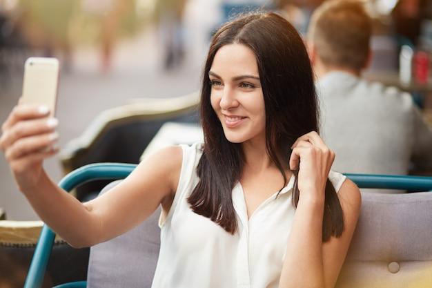 Jong vrouwelijk model met donker steil haar en zachte glimlach vormt voor het maken van selfie, zit tegen een terrasje, gebruikt een moderne smartphone. positieve blij europese vrouw in restaurant
