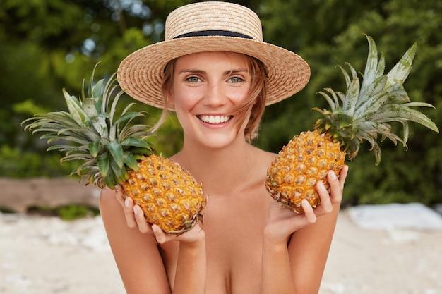 Jong vrouwelijk model poseert met twee exotische ananas