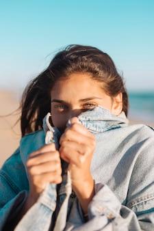 Jong vrouwelijk verbergend gezicht in het jasje van jean