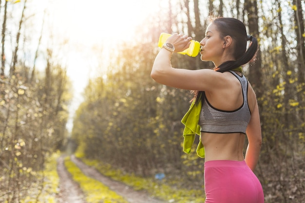 Jong vrouwen drinkwater in de aard