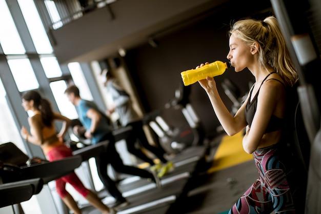 Jong vrouwen drinkwater in gymnastiek na training