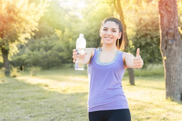 Jong vrouwen drinkwater na training, die goed voelen. actieve levensstijl.