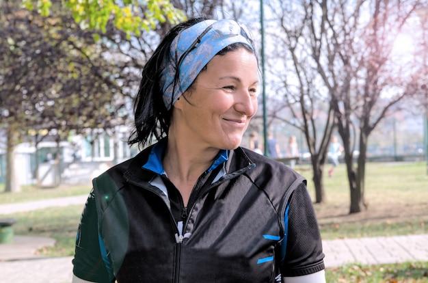 Jong vrouwen jogger portret in het park. sporten het midden oude vrouw glimlachen