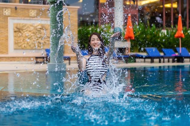 Jong vrouwen opspattend water in zwembad