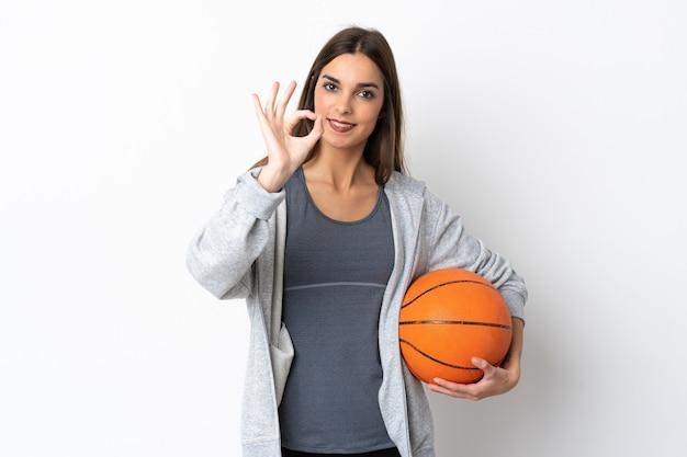 Jong vrouwen speelbasketbal dat op witte achtergrond wordt geïsoleerd die ok teken met vingers toont