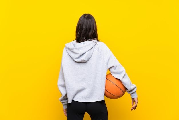Jong vrouwen speelbasketbal over geïsoleerde gele muur