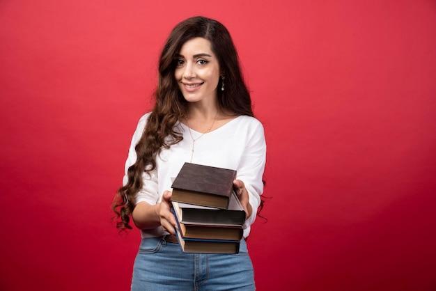 Jong vrouwenmodel dat boeken op een rode achtergrond aanbiedt. hoge kwaliteit foto