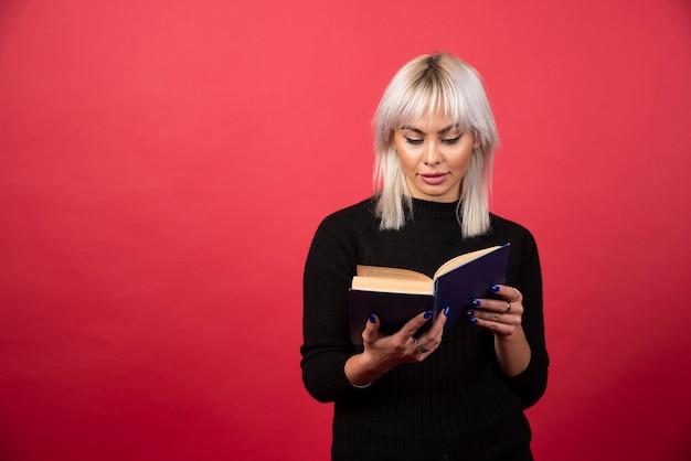 Jong vrouwenmodel dat een boek op een rode achtergrond leest. hoge kwaliteit foto