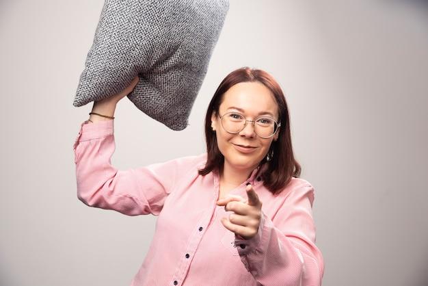 Jong vrouwenmodel dat een hoofdkussen op een witte achtergrond werpt. hoge kwaliteit foto