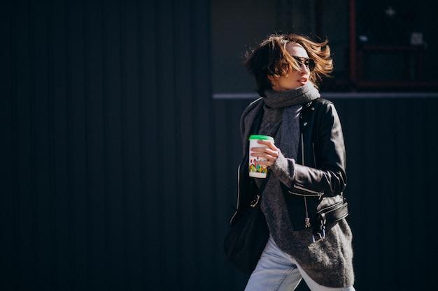 Jong vrouwenmodel in leerjasje buiten de straat