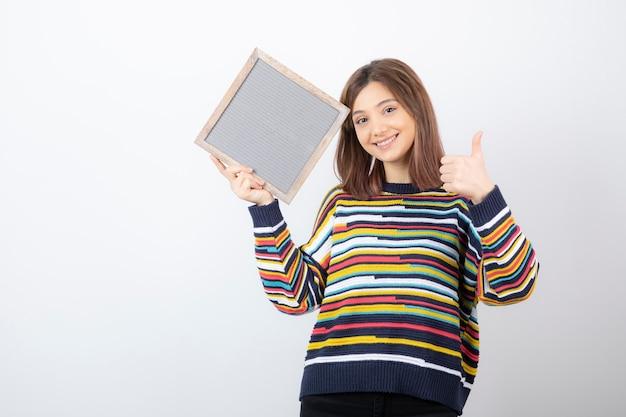 Jong vrouwenmodel met een frame dat een duim toont.