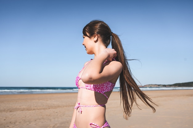 Jong vrouwenportret met een roze bikini op het strand