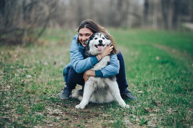 Jong vrouwenspel met schor hond voor een gang in de lentebos. lachen met plezier, blij met huisdier