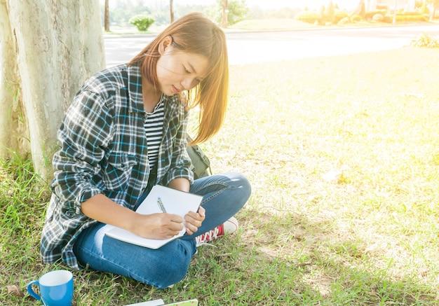 Jong vrouwenzitting die notitieboekje schrijven