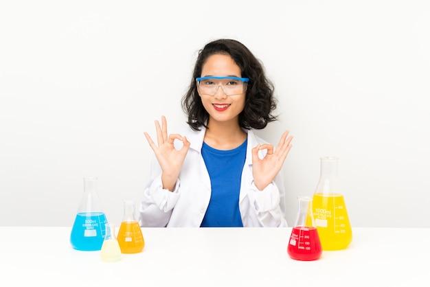 Jong wetenschappelijk aziatisch meisje dat een ok teken met vingers toont