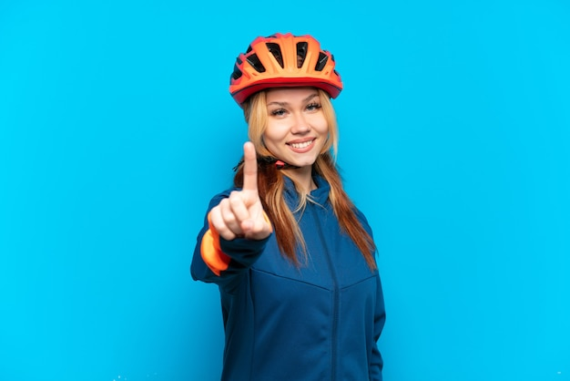 Jong wielrennermeisje dat op blauwe achtergrond wordt geïsoleerd die een vinger toont en opheft
